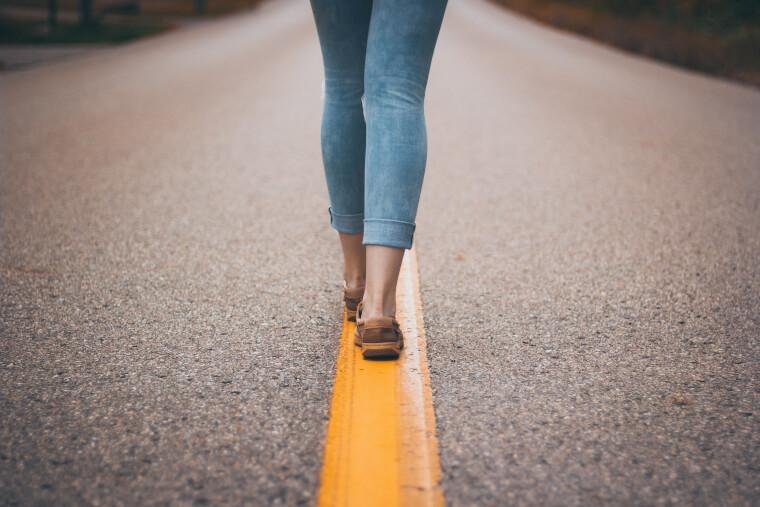 線を歩く女性